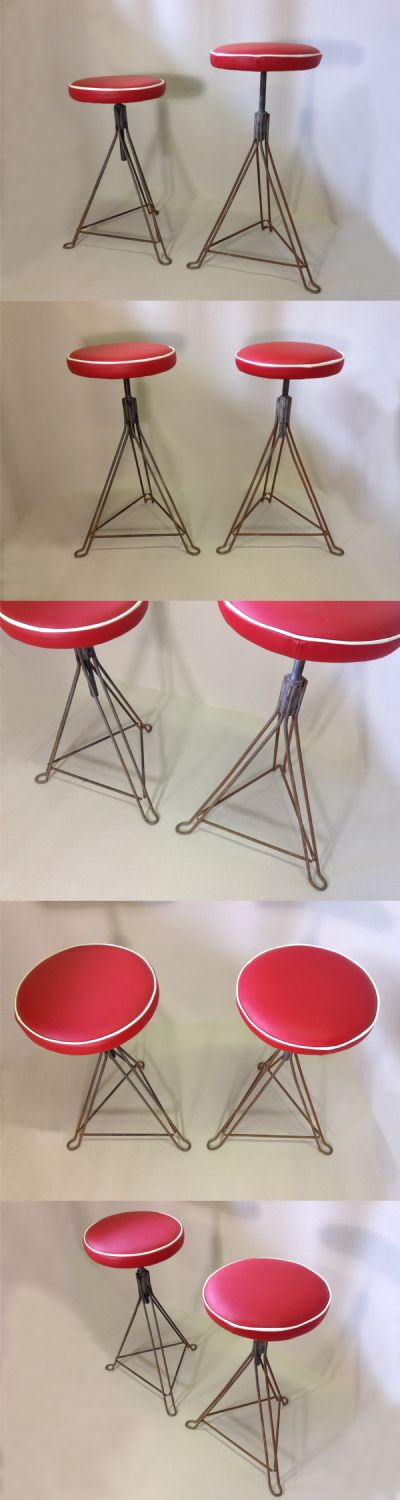 A pair of industrial metal framed stools, c1950s. Adjustable screw down bases. Upholstered in red leather.